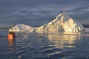 Soleil déclinant sur un iceberg d'Ilulissat à bord d'un bateau de pêche
